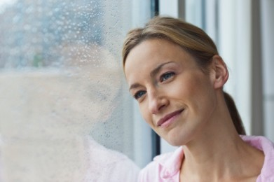 Woman looking out window on rainy day