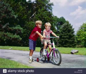 1960s-1970s-boy-helping-little-brother-ride-two-wheel-bicycle-with-BR9XDE