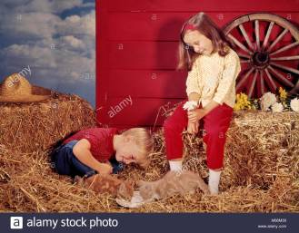 1960s-little-boy-and-girl-brother-and-sister-in-farm-barn-setting-M66M39