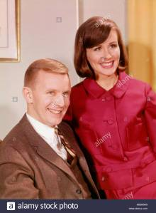 1960s-portrait-smiling-young-couple-man-in-business-suit-woman-wearing-M66MW9