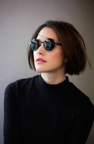 brown-haired-woman-with-straight-bob-parted-in-the-middle-wearing-black-round-sunglasses-and-black-top.jpg