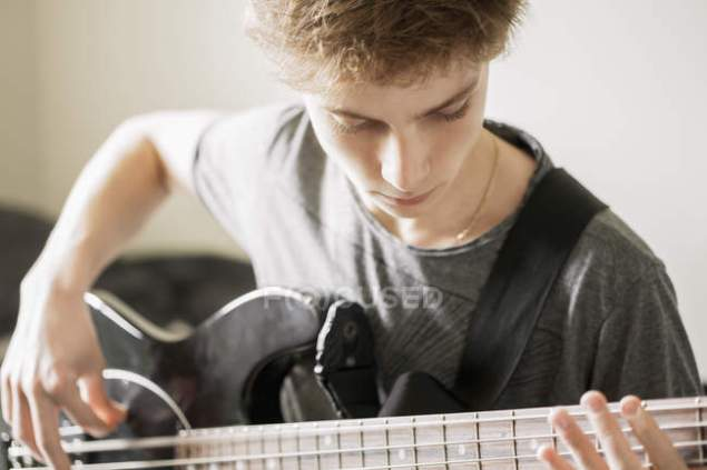 focused_222927622-stock-photo-teenage-boy-playing-guitar-selective