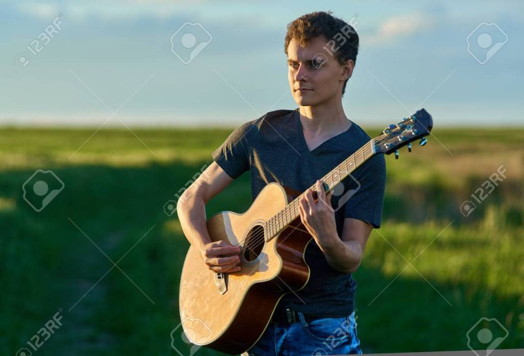 This image has an empty alt attribute; its file name is 78924825-teenage-boy-playing-guitar-at-sunset-in-a-wheat-field.jpg